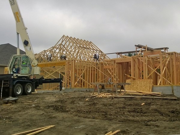 New custom home takes shape with roof trusses being installed
